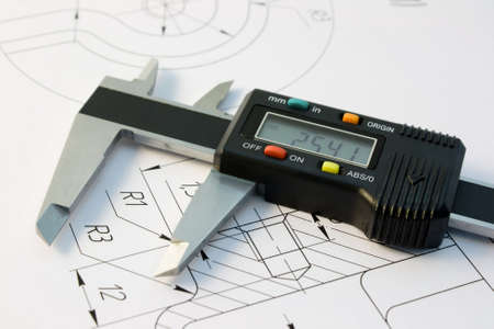 The electronic calliper lies on the detail drawing photo