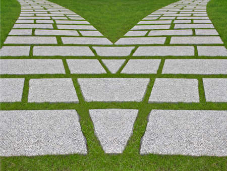 divergence: Way divergence. Granite plates on a green lawn. Stock Photo