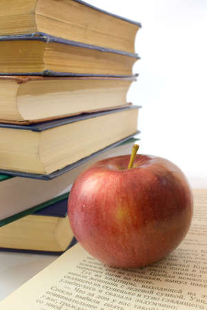 bibliography: Red apple and pile of books. Photo close up.