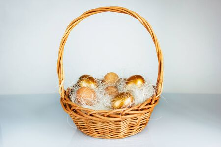 Easter golden eggs in a basket on table.