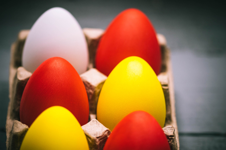 Easter spring composition, box with painted colorful eggs. Close up portrait on gray wooden background. Selective focus. Stock Photo