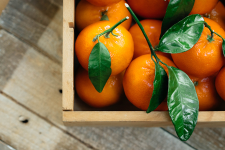 Tangerines oranges, clementines, citrus fruits with green leaves in a wooden box over light wooden background with copy space.