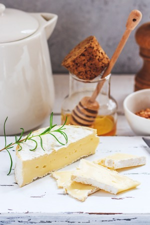 Cheese plate served with crackers, honey and nuts. Camembert on white wood serving board over white texture background