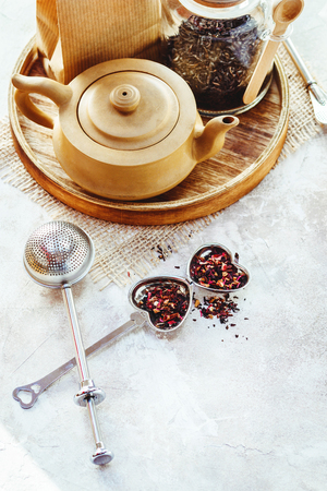 Ceramic tea pot, metal tea infuser and cup of black tea. Composition with tea accessories on a white background. Stock Photo