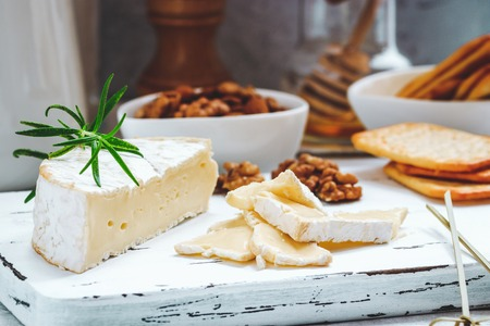 Cheese plate served with crackers, honey and nuts. Camembert on white wood serving board over white texture background. Appetizer theme Standard-Bild
