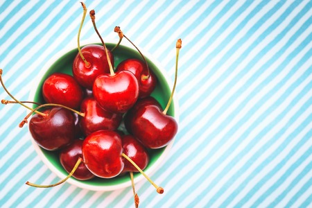 Sweet colorful fresh cherries in a bowl on white textured background, top view with copy space