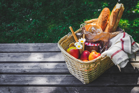 Picnic basket filled with fruit , bread and jar with apricot jam on wooden table