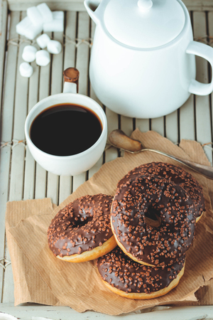 Chocolate donuts and coffee , weekend morning table. Breakfast on a wooden tray. Vintage colors.