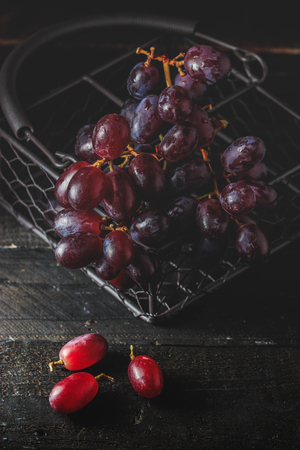 Red grape in metallic basket on black wooden background , dark mood