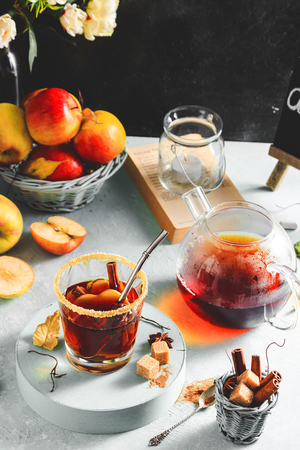 Apple cider drink, hot cocktail with cinnamon sticks and apple slices. Tea with spices. Autumn cozy mood