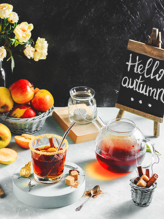 Apple cider drink, hot cocktail with cinnamon sticks and apple slices. Tea with spices. Autumn cozy mood.
