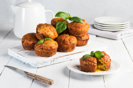 Homemade freefly baked double cheese muffins with basilic on a white wooden board. Healthy snack or breakfast meal Stock Photo