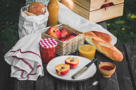 Assortment of food for picnic on wooden table. Plate with apricots, little jar with jam , variety of bread, glace of juice. Cozy summer breakfast