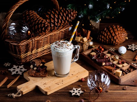 Hot chocolate drink with whipped cream. Cozy Christmas composition on a dark wooden background. Sweet treats for cold winter days.