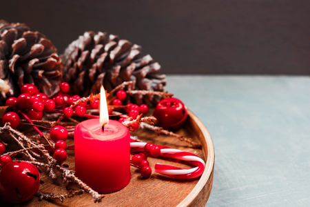 Seasonal and holidays concept. Decorative composition with candle, fir cones, winter background. Selective focus. Stock Photo