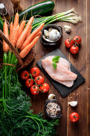 Healthy eating. Raw food concept. Vegetables and turkey fillet on wooden table. Top view Stock Photo
