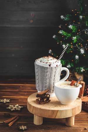 Cozy Christmas concept.Two mug with hot drinks, chocolate with whipped cream and cappuccino with cinnamon stick on a dark wooden background. Sweet treats for cold winter days. Stock Photo