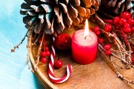 Seasonal and holidays concept. Decorative composition with candle, fir cones, winter background. Selective focus Stock Photo