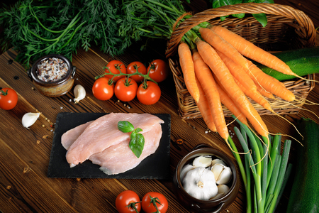 Healthy eating. Raw food concept. Fresh vegetables and turkey fillet on wooden table. Top view. Stock Photo