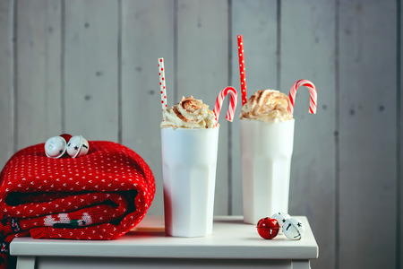 Cozy Christmas concept.Two mug with hot drinks, chocolate with whipped cream and cappuccino with cinnamon stick on a wooden background. Sweet treats for cold winter days.