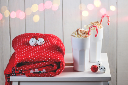 Cozy Christmas composition.Two mug with hot drinks, chocolate with whipped cream and Candy Canes in front of a light wooden background. Sweet treats for cold winter days