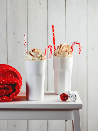 Cozy Christmas composition.Two mug with hot drinks, chocolate with whipped cream and Candy Canes in front of a light wooden background. Sweet treats for cold winter days.