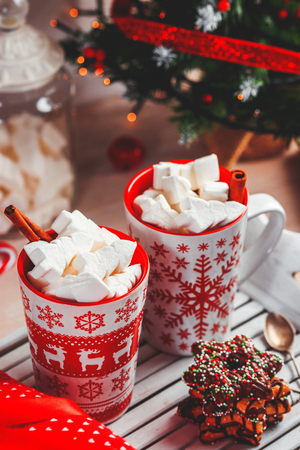 Two mugs with hot drink and marshmallows on the top. Christmas colorful still life. Cozy festive mood