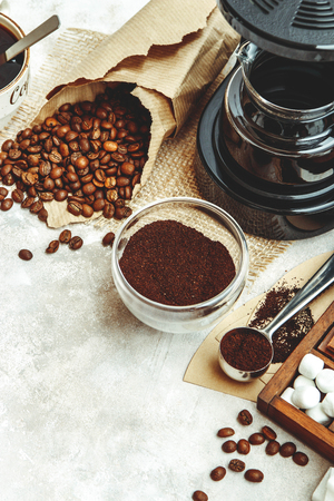 Variety things for prepare coffee. Roasted beans, ground coffee, scoop, electric coffee machine and assortment of sweets and spices to eat with on light background. Top view copyspace