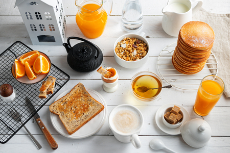 Healthy breakfast eating concept, various morning food - pancakes, soft-boiled egg, toast, oatmeal, granola, fruit, coffee, tea, orange juice milk on white wooden table. Top view Stock Photo
