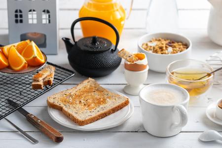Healthy breakfast eating concept, various morning food - pancakes, soft-boiled egg, toast, oatmeal, granola, fruit, coffee, tea, orange juice milk on white wooden table.