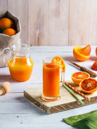 Glass of fresh pressed orange juice and blood oranges on wooden table. Bright summer mood Stock Photo