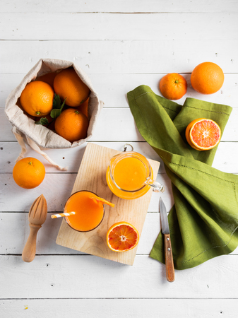 Glass of fresh pressed orange juice and blood oranges on wooden table. Bright summer mood. Top view.