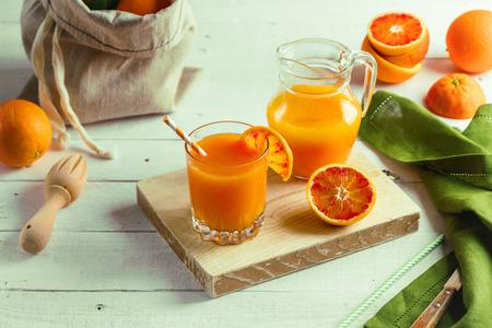 Glass of fresh pressed orange juice and blood oranges on wooden table. Bright summer mood Reklamní fotografie