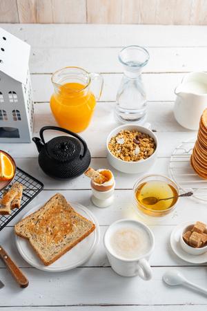 Healthy breakfast eating concept, various morning food - pancakes, soft-boiled egg, toast, oatmeal, granola, fruit, coffee, tea, orange juice milk on white wooden table. Top view Reklamní fotografie