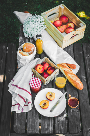 Assortment of food for picnic on wooden table. Plate with apricots, little jar with jam , variety of bread, glace of juice. Cozy summer breakfast. Stock Photo