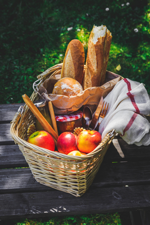 Picnic basket filled with fruit , bread and jar with apricot jam
