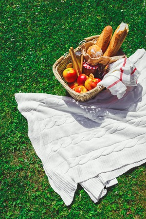 Hat, straw basket with food and drinks on beige plaid .