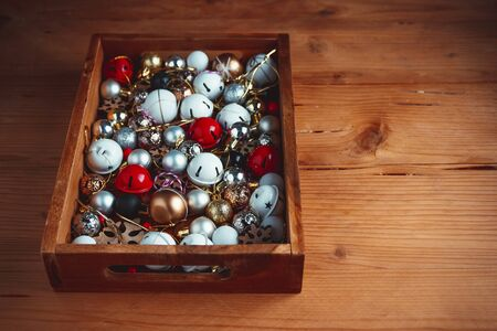 Wooden box full of christmas decorative elements, bows, toys.