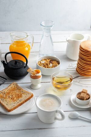 Healthy breakfast eating concept, various morning food - pancakes, soft-boiled egg, toast, oatmeal, granola, fruit, coffee, tea, orange juice, milk on white wooden table