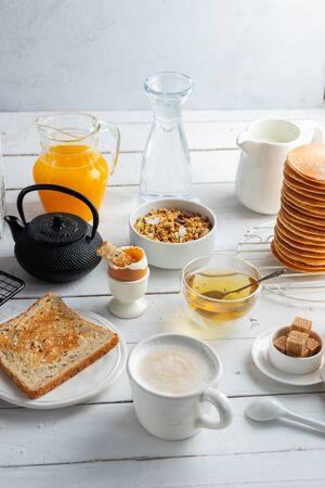 Healthy breakfast eating concept, various morning food - pancakes, soft-boiled egg, toast, oatmeal, granola, fruit, coffee, tea, orange juice, milk on white wooden table Stock Photo - 135583483