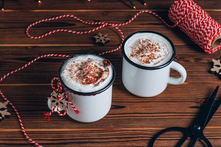 Cozy Christmas composition.Two mug with hot drinks, chocolate with whipped cream and cinnamon stick on a dark wooden background. Sweet treats for cold winter days