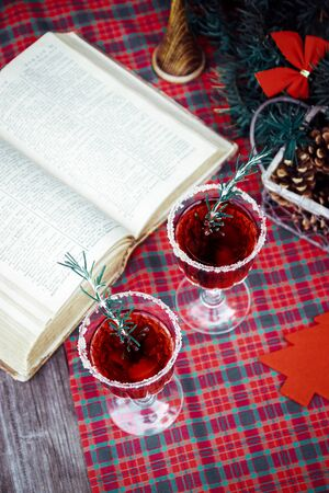 Christmas still life , two glass with red raspberry beverage decorated with rosemary , vintage old fashion style.