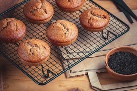 Homemade fresh banana and chocolate muffins on cooling rack Stock Photo - 132896728