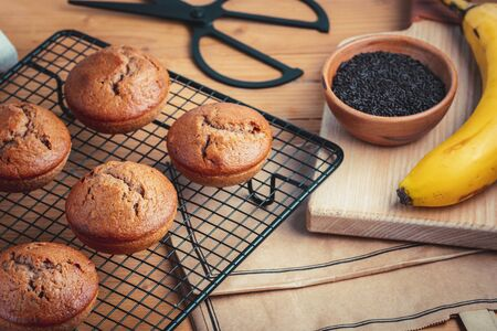 Homemade fresh banana and chocolate muffins on cooling rack Stock Photo - 132900531