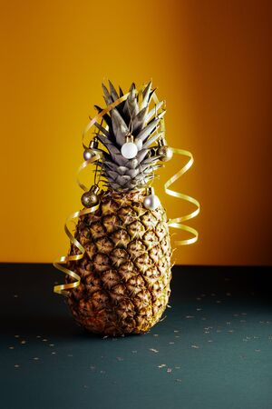 Pineapple decorated with serpentine and balls, holidays christmas and new year concept Stock Photo