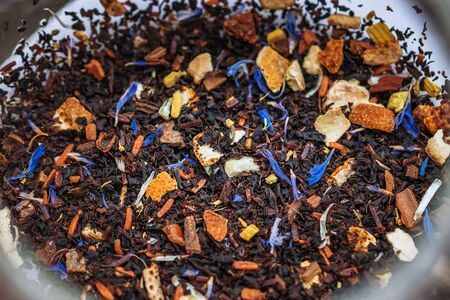 Close up of winter mix black tea tropical fruit cornflowers and spices in a teapot,