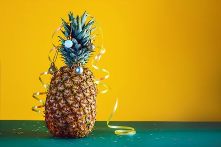 Pineapple decorated with serpentine and balls, holidays christmas and new year concept. Stock Photo - 134982972