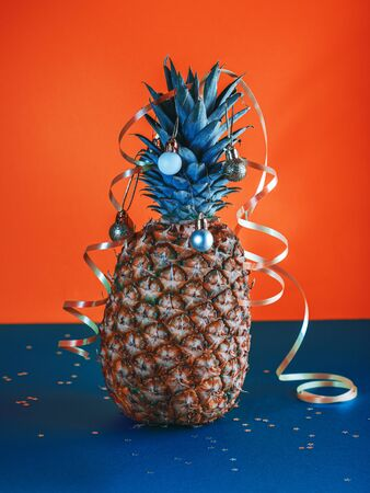 Pineapple decorated with serpentine and balls, holidays christmas and new year concept. Trendy 2020 colors