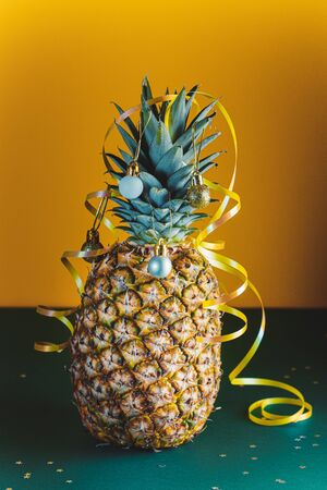 Pineapple decorated with serpentine and balls, holidays christmas and new year concept. Stock Photo
