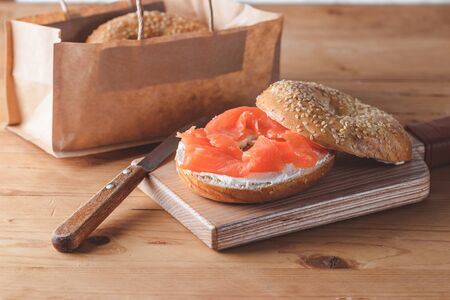 Fresh made Bagel with Salmon on old wooden table.